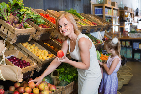 Portrait of smiling charming woman and cheerful cute girl buying fresh fruits in grocery shop