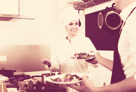 Smiling female cook in uniform standing on kitchen and giving fresh green salad to waitress