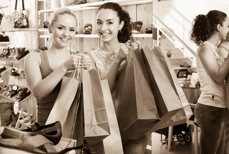 Two happy glad young women shopping shoes and looking happy with purchases. Focus on both persons Stock Photo