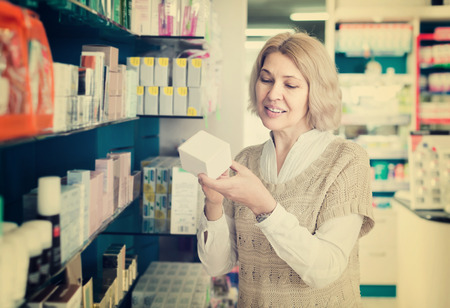 chooses: Portrait of russian mature woman chooses drugs at the pharmacy Stock Photo