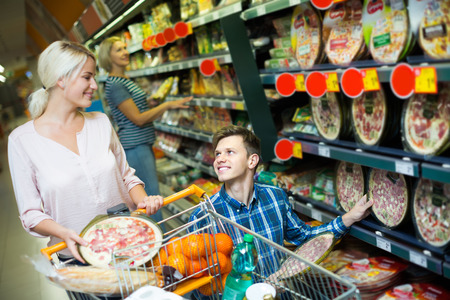 cooled: Smiling spouses buying Italian pizza in cooled food section
