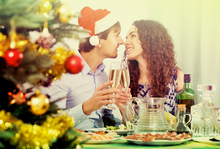 mirth: Young family celebrating Christmas at the table together Stock Photo