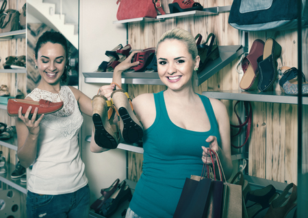 desires 25: smiling  girl holding a picked pair of shoes in the boutique