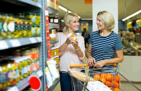 canned goods: Attractive women customers standing near shelves with canned goods at store