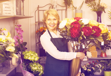selling service smile: Smiling positive female florist wearing an apron and happily holding big bouquet with peonies