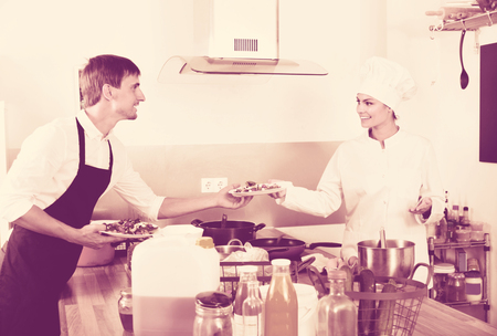 diligent: Portrait of diligent positive young smiling woman cook giving to waitress ready to serve salad