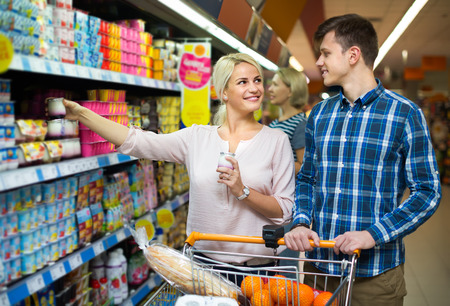 ordinary: Ordinary young family choosing dairy products and smiling in hypermarket