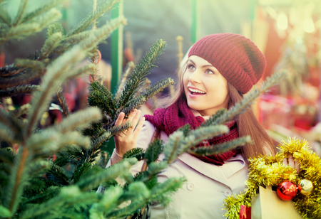 overspending: Happy woman buying Christmas tree in a market Stock Photo