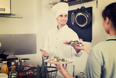 diligente: Portrait of diligent young  man cook giving to waitress ready to serve salad Foto de archivo