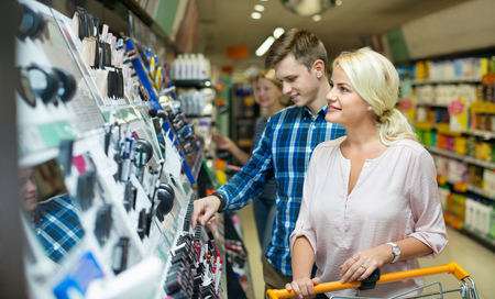 Positive young customers choosing beauty treatment in local supermarket