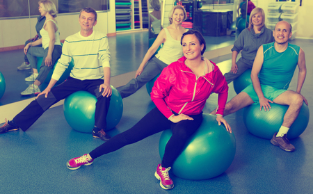 workouts: Group of joyful smiling  people training with balls in  fitness club . Selective focus