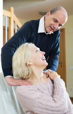 Happy pensioner sitting on sofa, husband massaging her neck Stock Photo