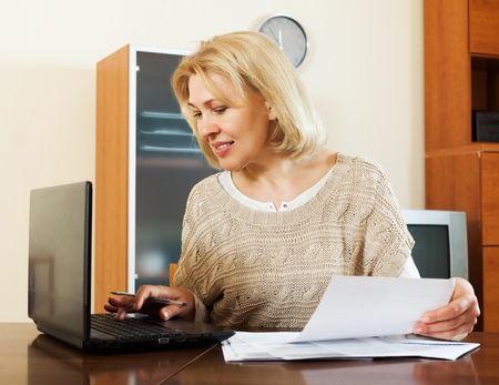 serious mature woman with notebook and financial documents at table at home