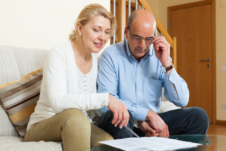 serious elderly couple with financial documents in home interior