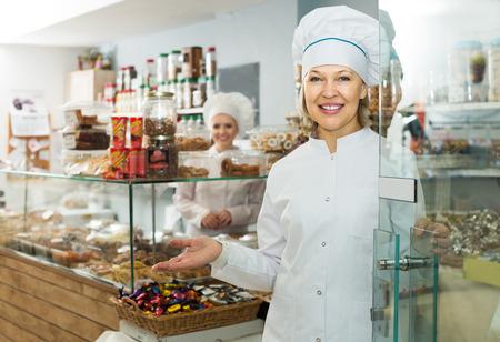 Glimlachende volwassen chef-koks met hoeden die klanten ontmoeten bij deur in patisserie