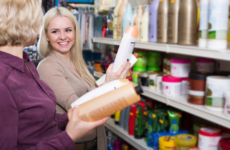 mother and young daughter in good spirits selecting shampoo in the store