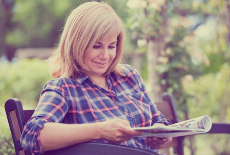 Portrait of cheerful mature woman sitting on bench and reading book outdoors in garden Stock Photo