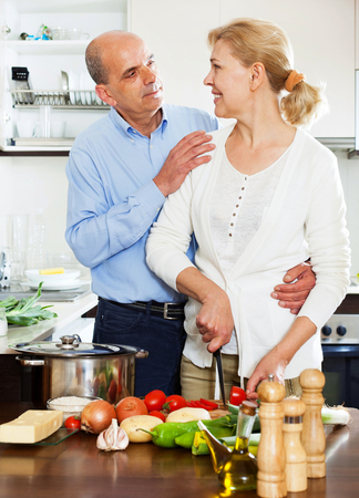 ordinary: happy ordinary mature couple cooking food with vegetables