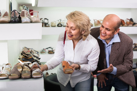 retirees: Two happy american  retirees together choosing pair of shoes in fashion store