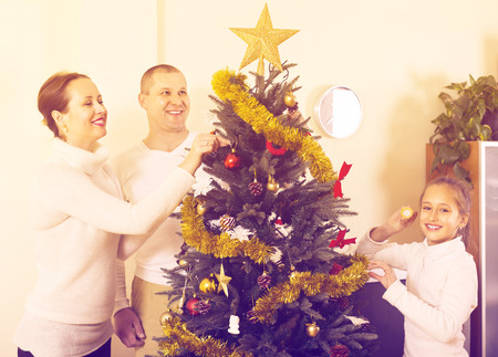 home decorating: Family with daughter decorating Christmas tree in the living room at home. Focus on woman