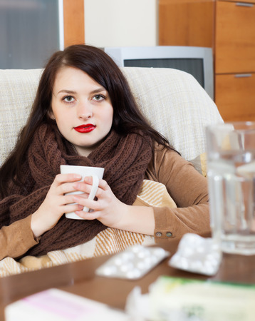 Ill woman with medications at living room Stock Photo