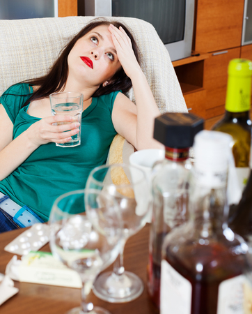 Suffering woman having headache after celebrating of holiday Stock Photo