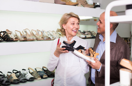 retirees: Two positive russian retirees together choosing pair of shoes in fashion store Stock Photo
