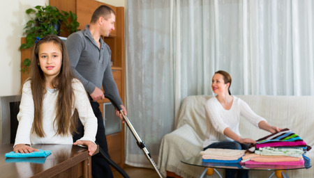 tidying up: Happy family of three tidying up a room all together. Focus on girl