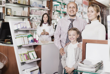 three persons: Cheerful smiling family of three persons getting help of pharmacist in a pharmacy
