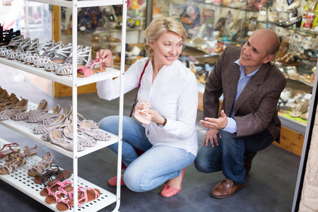 choise: Woman and man make choise between pink and beige sandals in shoe shop Stock Photo