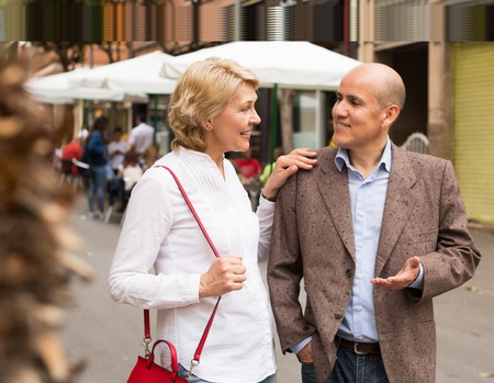 argumentation: Portrait of smiling mature couple walking and chatting in town Stock Photo