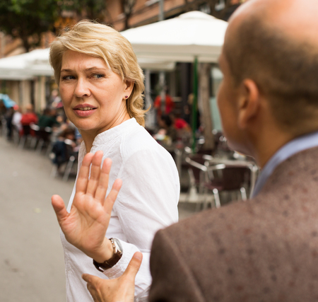 argumentation: annoyed retiree woman stopping dialog by hand gesture outdoors