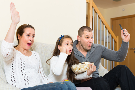 Parents and daughter watching TV show together and smiling indoors. Focus on girl
