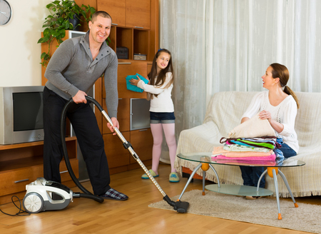 tidying up: Positive smiling family of three tidying up a room all together. Focus on man