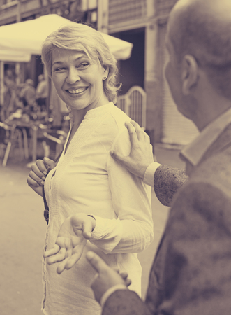 argumentation: Portrait of smiling mature woman walking in town and stopped by man
