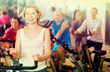 lifestile: Woman on fitness cycle with group of people
