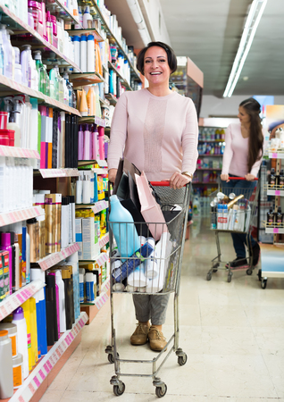 Mature smiling woman standing with shopping cart and choosing goods in cosmetics store