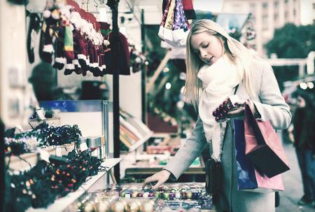 overspending: Smiling blonde girl shopping at festive fair before Xmas