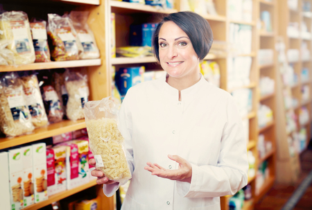 cereals holding hands: Smiling mature woman seller in uniform holding cereals products in hands near shelfs