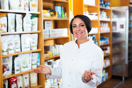 biologically: Portrait of cheerful mature female pharmacist in biologically active dietary supplements store Stock Photo
