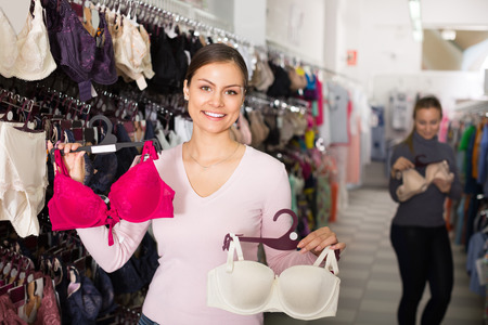 Cheerful young brunette woman selecting new bra in lingerie department
