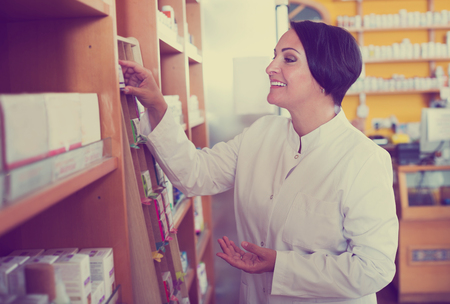 biologically: Portrait of positive mature female pharmacist in biologically active dietary supplements store Stock Photo