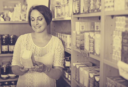 mature brunette: Happy pleasant smiling mature brunette woman having health supplements in box in drugstore Stock Photo