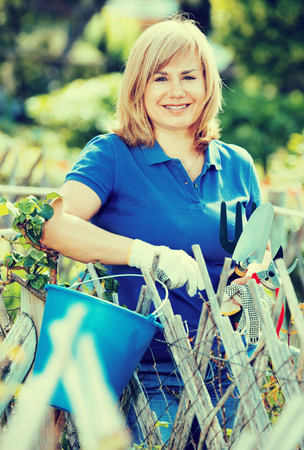 horticultural: Smiling pleasant blond mature woman  holding horticultural tools in garden on sunny day