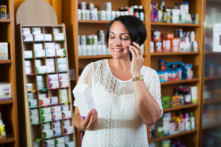 Portrait of cheerful mature woman talking using her phone in healthy food store Stock Photo