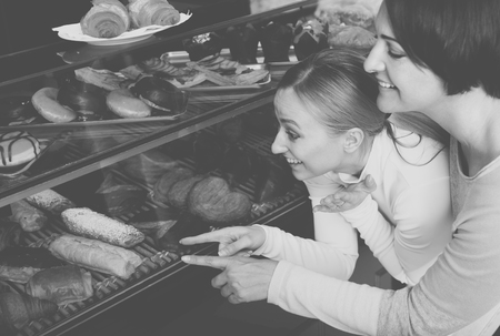 gladly: Girl and woman gladly selecting pastry in the bakery Stock Photo