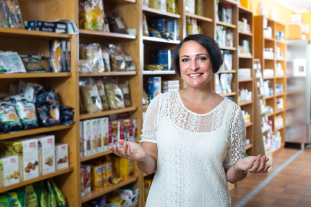 dietary supplements: ?Smiling mature woman customer buying dietary supplements in food store Stock Photo