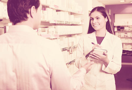 farmacy: Smiling pharmacist counseling customer about drugs usage in modern farmacy