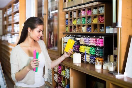 chandler: Young cheerful woman shopping multicolored candles in craft store