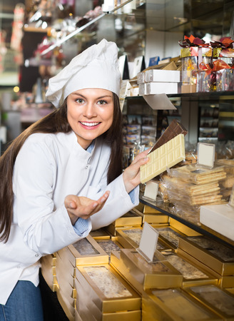 shopgirl: Young shopgirl posing with different delicious chocolate and confectionery at display